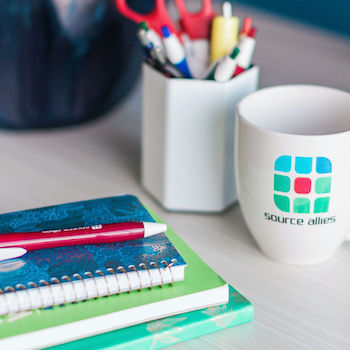 An inviting desk space complete with a white coffee mug with the Source Allies logo on it, a plant, a stack of notebooks, and a pen.
